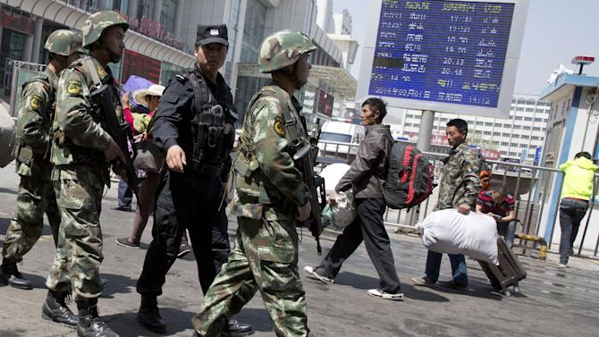 """Heavily armed Chinese paramilitary policemen march past the site of the Wednesday's explosion outside the Urumqi South Railway Station in Urumqi in northwest China's Xinjiang Uygur Autonomous Region Thursday, May 1, 2014. Chinese President Xi Jinping has demanded 'decisive actions"""" against terrorism following the attack at the railway station in the far west minority region of Xinjiang that left three people dead and 79 injured. (AP Photo/Ng Han Guan)"""