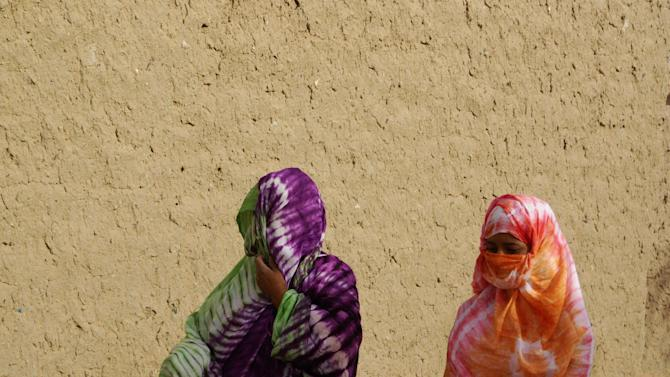 In this Tuesday, May 1, 2012 photo, women walking along a street wear veils in accordance with the directives of Islamist group Ansar Dine, which is seeking to impose Shariah law on Mali's Tuareg-occupied north, in Timbuktu, Mali. While government soldiers were fighting each other this week for control of the capital Bamako, Islamist fighters were asserting control over the Texas-sized northern half of the country, setting up a possible showdown with Tuareg nationalist rebels, who are secular and who seized northern Mali in March alongside the Islamists. (AP Photo)