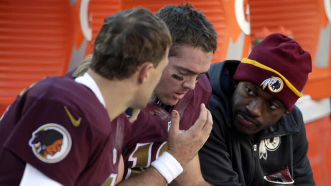 Washington Redskins quarterback Kirk Cousins, left, sits on the bench with quarterback Colt McCoy and quarterback Robert Griffin III, right, during the second half of an NFL football game against the Tennessee Titans, Sunday, Oct. 19, 2014, in Landover, Md. The Redskins won 19-17. (AP Photo/Pablo Martinez Monsivais)