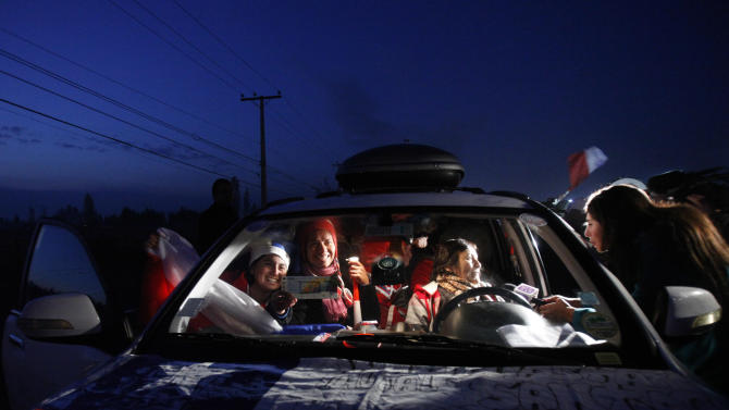 Chile soccer fans are illuminated by lights from a local TV station as they are interviewed in their car just before departing with a caravan for the World Cup in Brazil, from Santiago, Chile, early Friday June 6, 2014. Held every four years, the World Cup hasn't been in the Americas since 1994, when the United States played host. For many, this is a once in a lifetime chance to cheer their national teams in person. (AP Photo/Luis Hidalgo)