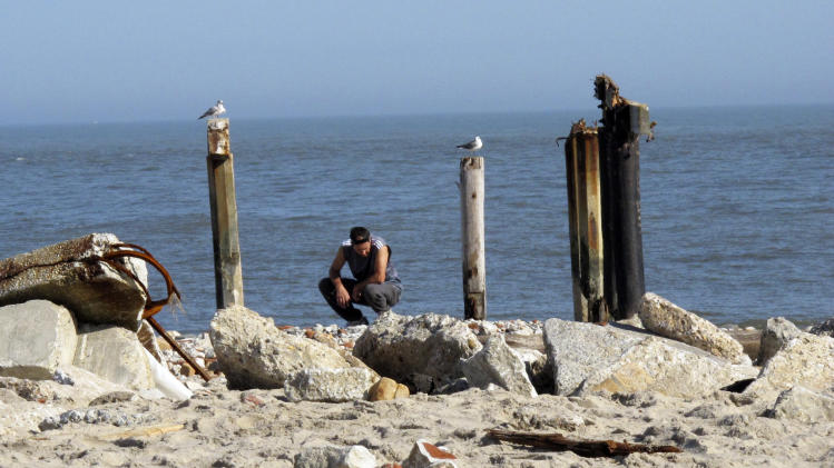 In this Monday, Nov. 12, 2012 photo, a man squats in the rubble of an oceanfront neighborhood in Atlantic City N.J. Two weeks after Superstorm Sandy hit the region, many of Atlantic City's poorest residents are enduring its aftermath with quiet acceptance and gratitude for the help being offered to them. (AP Photo/Wayne Parry)