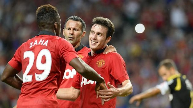 Manchester United's Chilean striker Angelo Henriquez (R) celebrates teammate midfielder Ryan Giggs (C) and midfielder Wilfried Zaha (L) after scoring during the friendly football match AIK vs Manchester United (AFP)