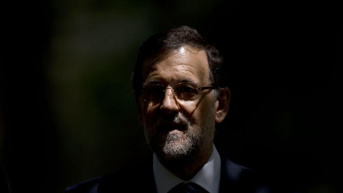 Spain's Prime Minister Mariano Rajoy is lit by a sun ray as he walks underneath trees with Romania's Prime Minister Victor Ponta, not seen, before a meeting at the Moncloa Palace in Madrid, Monday, July 22, 2013. Opposition leaders called for Rajoy to explain himself before Parliament or face a censure vote. Rajoy brushed off demands he should resign after text messages emerged showing him comforting a former political party treasurer under investigation over a slush fund and secret Swiss bank accounts. The treasurer has claimed Rajoy took under-the-counter payments, accusations denied by Rajoy. (AP Photo/Daniel Ochoa de Olza)