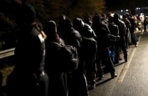 Migrants stay in a queue after crossing the Austrian-German border from Achleiten, Austria, in Passau