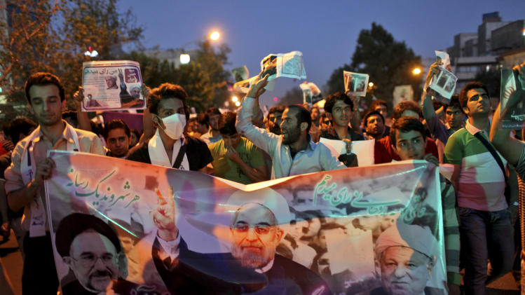 Supporters of the Iranian presidential candidate Hasan Rowhani, former Iranian nuclear negotiator, chant slogans, as they hold a banner containing pictures of Rowhani, center, former Presidents Akbar Hashemi Rafsanjani, right, and Mohammad Khatami, during a street campaign, in Tehran, Iran,Wednesday, June 12, 2013. The presidential election will be held on June 14. (AP Photo/Ebrahim Noroozi)