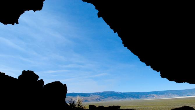 File--This July 23, 2008, file photo, shows the sagebrush desert of Summer Lake Basin and Winter Ridge  silhouetted by one of the Paisley Caves near Paisley, Ore.  Stone tools and human DNA from the ancient Oregon caves offer new evidence of how the first Americans spread through the continent--archaeologists reported Thursday, July 12, 2012, that they have dated broken spear points from the cave to about 13,200 years ago, as old as much different stone tools found elsewhere from the better-known Clovis culture found in the southeast and interior United States.(AP Photo/Jeff Barnard, file)
