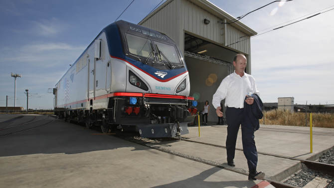 In this photo taken Saturday, May 11, 2013, Michael Cahill, president of Siemens Rail Systems, walks past one of  the new Amtrak Cities Sprinter Locomotive that was built by Siemens in Sacramento, Calif. The new electric locomotive, one of three of 70 to be built,  will run on the Northeast intercity rail lines and  replace Amtrak locomotives that have been in service for 20 to 30 years.(AP Photo/Rich Pedroncelli)
