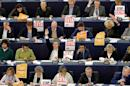 """MEPs display posters with the words """"stop CETA"""" as they take part in a voting session at the European Parliament in Strasbourg"""