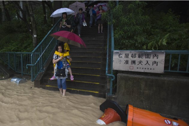 A mother carries her daughter while wading through waters in Hong Kong