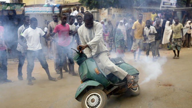 "Nigerians  celebrate the anticipated victory of Presidential candidate Muhammadu Buhari  by doing a burnout on a scooter in Kaduna,  Nigeria Tuesday, March 31, 2015. The spokesman for retired Gen. Muhammadu Buhari says the former military dictator has won Nigeria's bitterly contested presidential election but fears ""tricks"" from the government. Garba Shehu tells The Associated Press that their polling agents across the country tell them they have succeeded in defeated President Goodluck Jonathan.(AP Photo/Jerome Delay)"