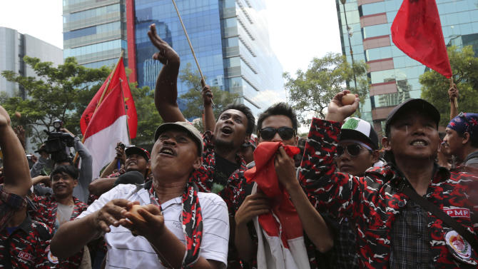 """Indonesian protesters throw eggs during a demonstration outside Australian Embassy in Jakarta, Friday, Nov. 22, 2013. Indonesia has """"downgraded"""" its relations with Australia and suspended cooperation on people smuggling following outrage over reported eavesdropping on senior Indonesian leaders' phones, officials said Wednesday. (AP Photo/Tatan Syuflana)"""