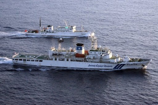 A Japan coast guard vessel (bottom) monitors a Chinese fisheries boat (top) near the disputed Senkaku or Diaoyu islands