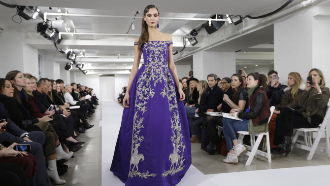 De la Renta takes bow with models on his arm