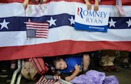 A young boy watches US Republican presidential candidate Mitt Romney holding a rally at Pensacola Civic Center in Pensacola, Florida. With the storm -- dubbed &quot;Frankenstorm&quot; -- now stalking the US East Coast, Romney canceled all his scheduled rallies in battleground Virginia Sunday to get out of the way of frantic preparations for the fierce weather system, instead returning to Ohio