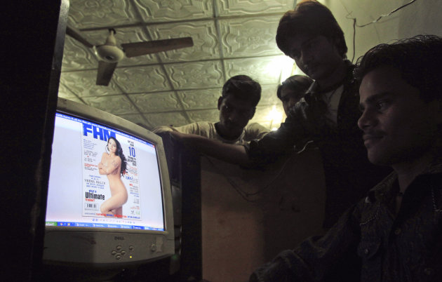 EDS NOTE: PARTIAL NUDITY - Pakistanis look at a website displaying Veena Malik's photo on the website of FHM India, at an Internet cafe in Karachi, Pakistan, Saturday, Dec. 3, 2011. Malik, a Pakistani
