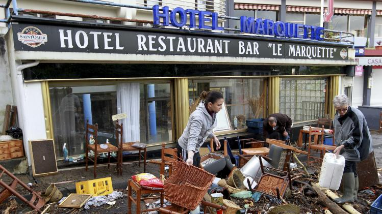 People clean their restaurant following floods in Lourdes, southwestern France, Wednesday, June 19, 2013. French rescue services and police are evacuating hundreds of pilgrims from hotels threatened by floodwaters from a rain-swollen river in the Roman Catholic shrine town of Lourdes. (AP Photo/Bob Edme)