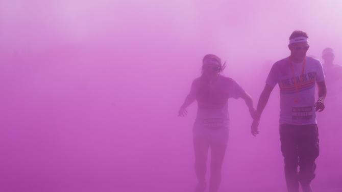 Competitors are showered with colour powders as they participate in the Color Run in Brighton