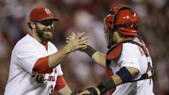 St. Louis Cardinals' Jason Motte (30) celebrates with catcher Yadier Molina after Game 5 of baseball's National League championship series against the Milwaukee Brewers Friday, Oct. 14, 2011, in St. Louis. The Cardinals won 7-1 to take a 3-2 lead in the series. (AP Photo/Matt Slocum)
