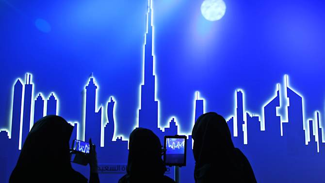 Emirati attendees take photos of an image of the city's skyline in Dubai, United Arab Emirates, Wednesday, March 5, 2014. After years of chasing the biggest and the best, the fast-growing Mideast city of Dubai is turning to technology to help the little things in life run more smoothly. (AP Photo/Kamran Jebreili)