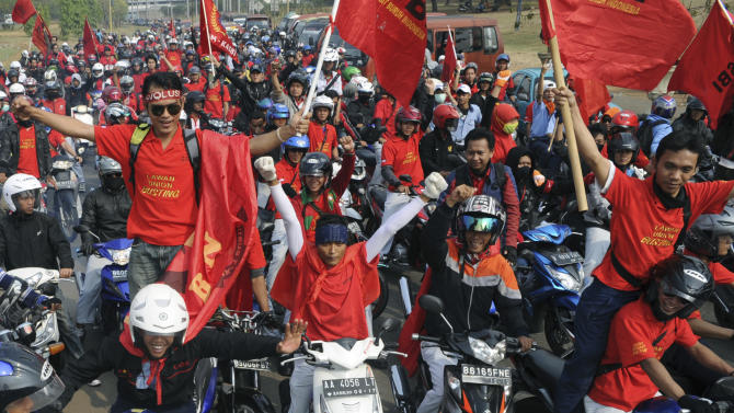Factory workers take part in a protest in Cikarang, West Java, Indonesia, Wednesday, Oct. 3, 2012. Indonesian unions said more than 2 million factory workers have gone on a one-day strike across the country to call for higher wages and protest the hiring of contract workers. (AP Photo)