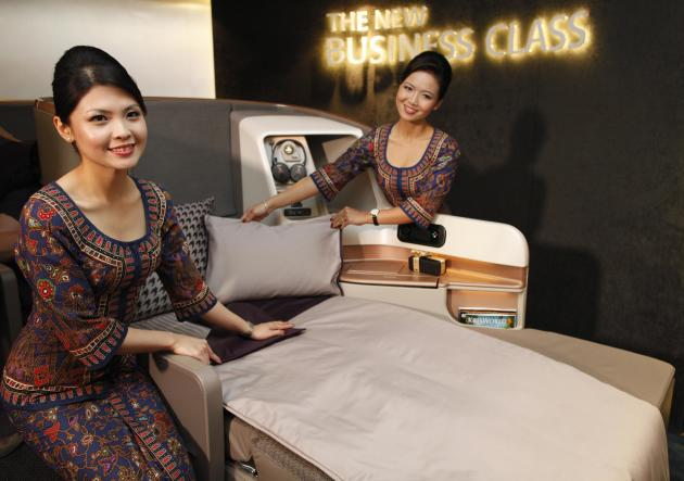Singapore Airlines Ltd stewardesses pose next to a business class seat during the launch of their new generation of cabin products at Changi Airport in Singapore