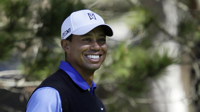 Tiger Woods smiles before hitting from the 16th tee at Spyglass Hill Golf Course during the first round of the AT&T Pebble Beach National Pro-Am golf tournament in Pebble Beach, Calif., Thursday, Feb. 9, 2012. (AP Photo/Marcio Jose Sanchez)