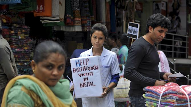 A Nepalese student asks for donation for the survivors of Saturday's earthquake during a vigil at a marketplace in Bengaluru