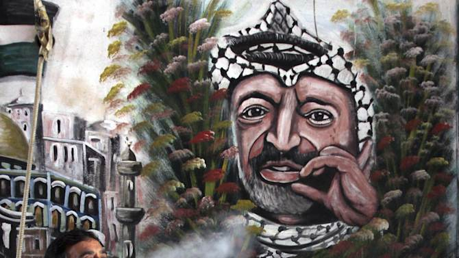 A Palestinian man smokes a water-pipe next to a mural of late Palestinian leader Yasser Arafat, in the West Bank town of Jenin, Tuesday, Nov. 27, 2012. Palestinian authorities on Tuesday opened Yasser Arafat's grave and foreign experts took samples from his remains as part of a long-shot attempt to determine whether he was poisoned, as relatives and some political successors have claimed. (AP Photo/Mohammed Ballas)