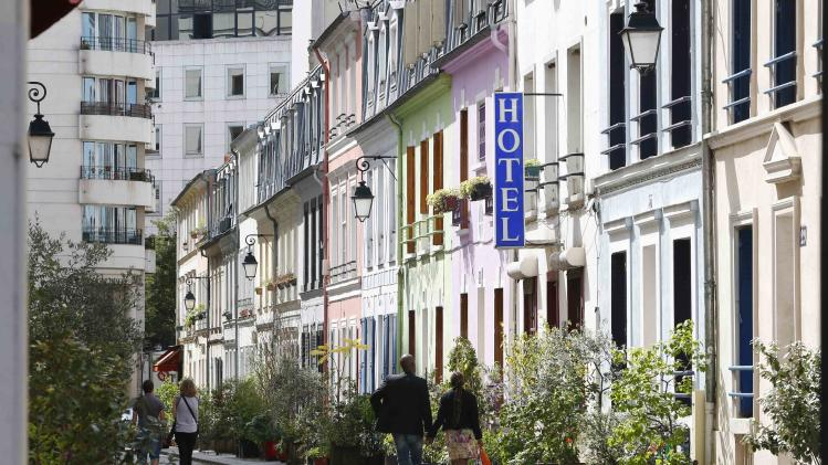 "A view shows people walking rue Cremieux, a street lined with colorful, terraced homes, and the hotel ""L'Hotel Particulier"" located in the 12th district of Paris"