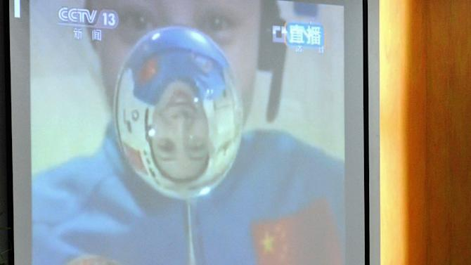 In this image released by China's Xinhua News Agency, students watch the live video broadcast of a space lecture by female astronaut Wang Yaping, seen on the screen, at Baochuta Experimental School in Hangzhou, China's Zhejiang Province, Thursday, June 20, 2013. China's astronauts struck floating martial arts poses and twirled gyroscopes during their first classroom lecture from the country's orbiting space station, part of efforts to popularize the successful manned space flight program among young people.(AP Photo/Xinhua, Ju Huanzong) NO SALES
