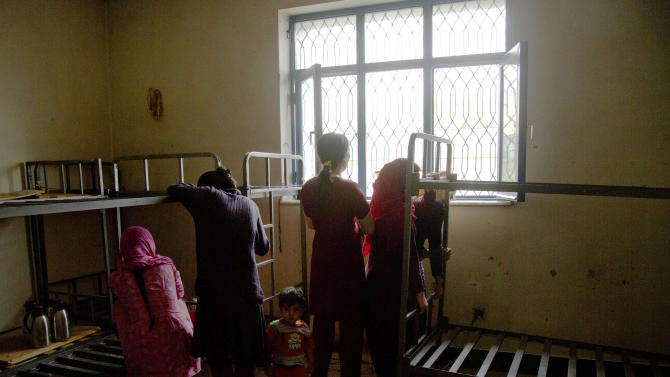 "Picture taken March 28, 2013 shows Afghan female prisoner peering through the window in their cell at Badam Bagh, Afghanistan's central women's prison, in Kabul, Afghanistan. Two hundred-and-two women living in the six- year- old jail, the majority of the women are serving sentences of up to seven years for leaving their husbands, refusing to accept a marriage arranged by their parents, or choosing to leave their parent's home with a man of their choice, all so-called ""moral"" crimes(. AP Photo/Anja Niedringhaus)"