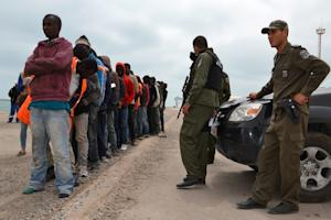 Migrants stand next to Tunisian security forces in…