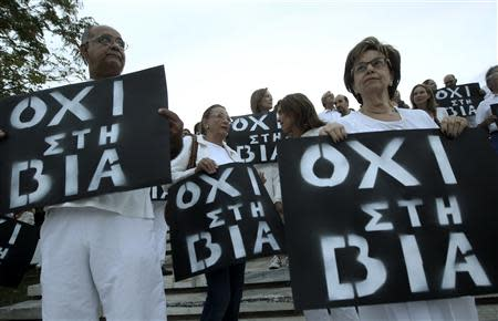 Protesters hold placards during an anti-violence rally following the killing of Greek rapper Pavlos Fissas by a supporter of the far-right Golden Dawn party, in Athens