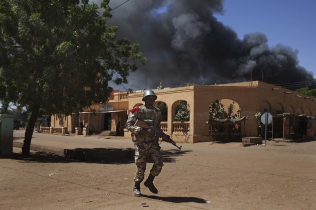 A Malian soldier runs past smoke from a petrol station on fire during fighting with Islamists in Gao