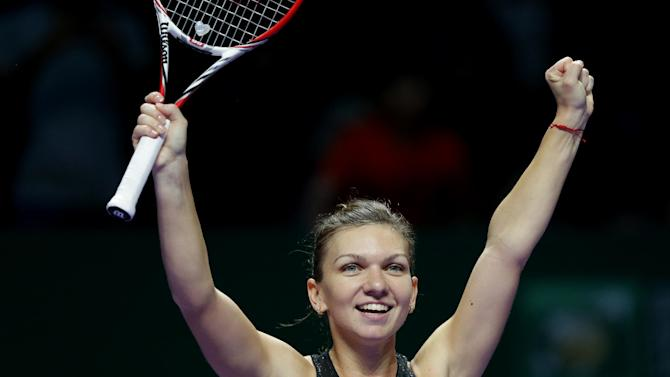 Romania's Simona Halep celebrates after defeating Serena Williams of the U.S. in their singles match at the WTA tennis finals in Singapore, Wednesday, Oct. 22, 2014. (AP Photo/Mark Baker)