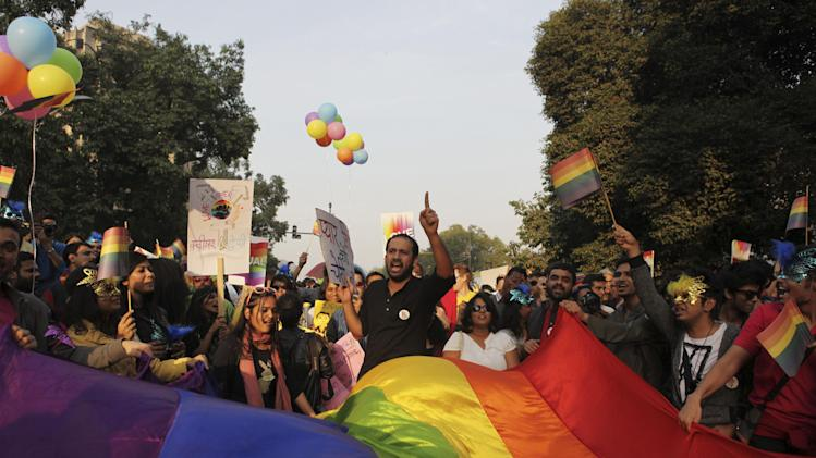FILE- In this Nov. 24, 2013 file photo, Indian gay rights activists display rainbow-colored banner and shout slogans as they march in New Delhi, India. A colonial-era law criminalizing homosexuality will remain in effect in India, a top court said Wednesday, dealing a blow to gay activists who have argued for years for the chance to live openly in India's deeply conservative society.(AP Photo/Tsering Topgyal, File)