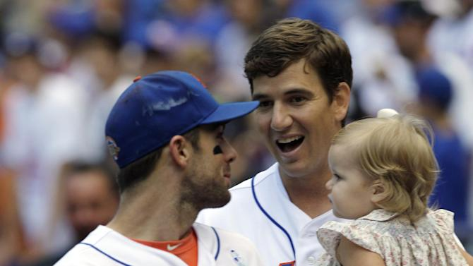 New York Giants quarterback Eli Manning, right, holds his daughter Ava as he chats with New York Mets third baseman David Wright, left, after throwing out the ceremonial first pitch on Father's Day before a baseball game against the Cincinnati Reds at Citi Field in New York, Sunday, June 17, 2012. (AP Photo/Kathy Willens)