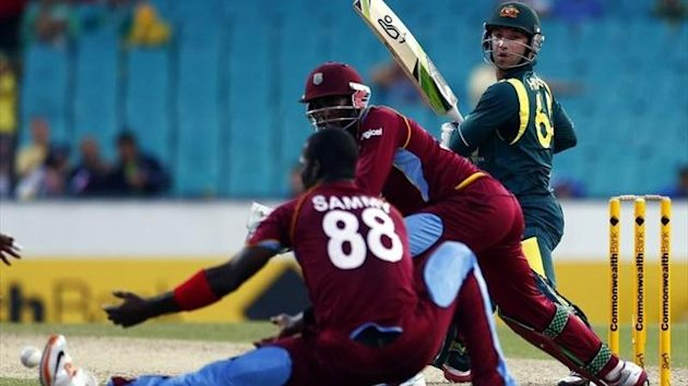 West Indies captain Darren Sammy (L) reaches to field a shot from Australia's Phillip Hughes (R) during their limited overs international cricket match at the Sydney Cricket Ground (AFP)