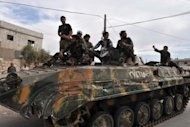 "Syrian rebel fighters celebrate on top of a tank captured from the Syrian army, in Maaret al-Numan, in the northwestern province of Idlib, an area under the control of rebel fighters, on October 17. International peace envoy Lakhdar Brahimi has warned that the Syria conflict risks setting the region ""ablaze"", as clashes broke out across the border with Lebanon"