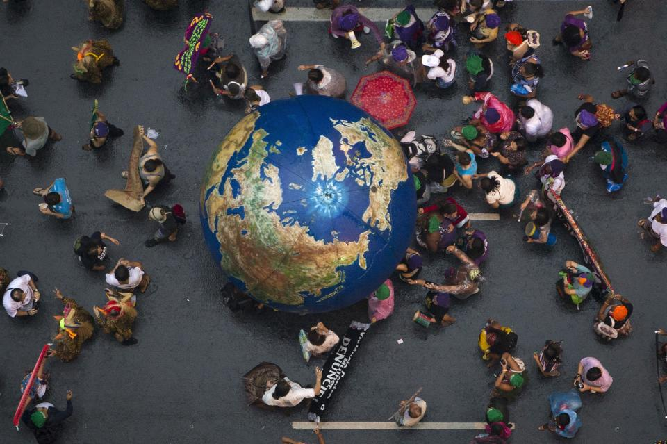 "Activists push an inflatable globe during a ""Global March"" as part of the People's Summit for Social and Environmental Justice in Defense of the Commons, a parallel event during the UN Conference on Sustainable Development, or Rio+20, in Rio de Janeiro, Brazil, Wednesday, June 20, 2012. (AP Photo/Felipe Dana)"