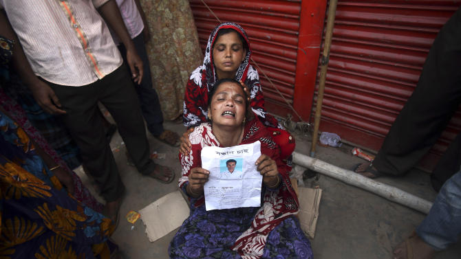 A woman grieves for her son who was trapped in the collapsed garment factory building and managed to survive for three days while being fed food and water passed to him by rescue workers but died later, Tuesday 30, April, 2013 in Savar, near Dhaka, Bangladesh. Emergency workers hauling large concrete slabs from the collapsed eight-story building said Tuesday they expect to find many dead bodies when they reach the ground floor. (AP Photo/Wong Maye-E)