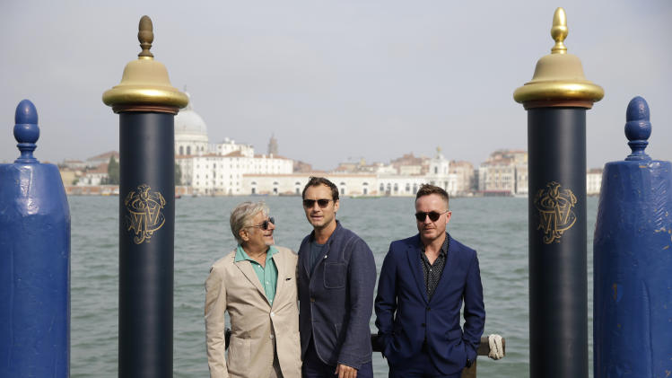 From left actors Giancarlo Giannini, Jude and cinematographer Jake Scott pose for photographers at The Cipriani hotel to promote the short film, The Gentlemen's Wager, made in partnership with Johnnie Walker Blue Label, during the 71st edition of the Venice Film Festival in Venice, Italy, Wednesday, Aug. 27, 2014. The 71st edition of the festival opens on Wednesday, Aug. 27th and runs until Sept. 6. (AP Photo/Andrew Medichini)