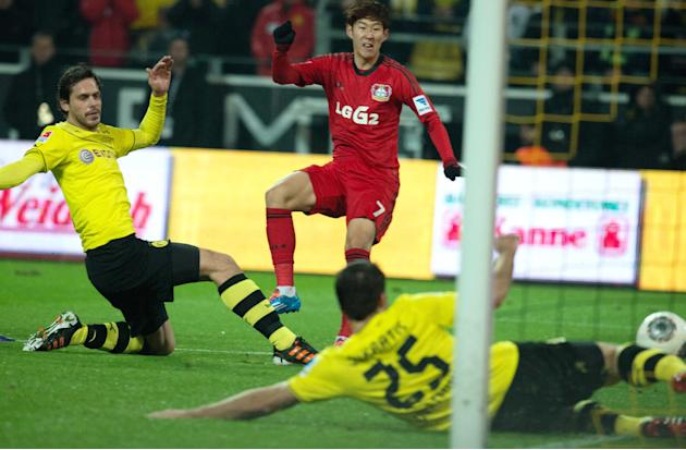 In this picture taken Saturday Dec. 7, 2013, South Korea's Son Heung-min, center,  scores  a goal while Dortmund's Manuel Friedrich, left, and Sokratis  try to defend during the German Bundesl