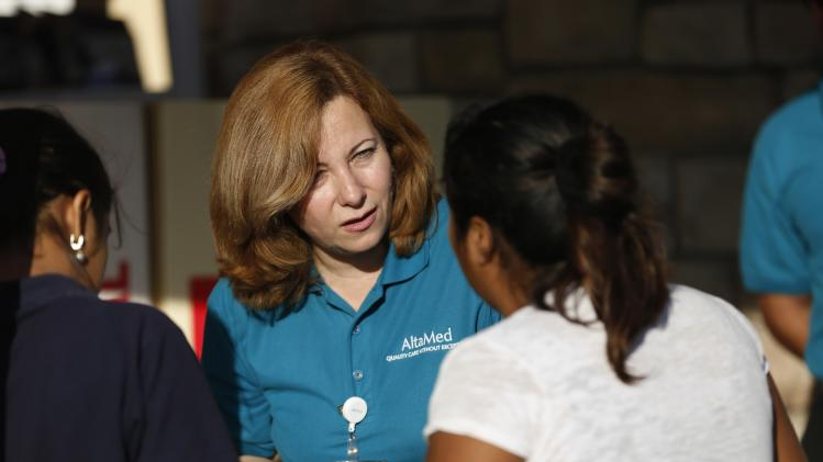 Corona, patient care coordinator at AltaMed, speaks to people during a community outreach on Obamacare in Los Angeles