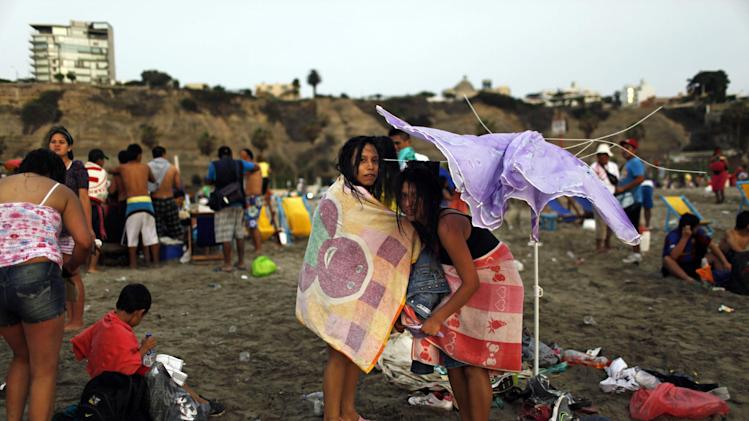 In this Jan. 13, 2013 photo, girls dress under a damaged umbrella on Agua Dulce beach in Lima, Peru. While Lima's elite spends its summer weekends in gate beach enclaves south of the Peruvian capital, the working class jams by the thousands on a single municipal beach of grayish-brown sands and gentle waves. The only barrier to entry to Agua Dulce beach is two dollars, the price of bus fare to get there and home. (AP Photo/Rodrigo Abd)