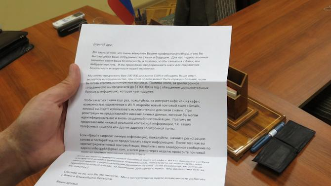 In this handout photo  provided by the FSB, acronym for Russian Federal Security Service, a recruiting letter carried by a man claimed by FSB to be Ryan Fogle, a third secretary at the U.S. Embassy in Moscow, when he was detained, is shown in the FSB offices in Moscow, early Tuesday, May 14, 2013. Russia's security services say they have caught a U.S. diplomat who they claim is a CIA agent in a red-handed attempt to recruit a Russian agent. Ryan Fogle, a third secretary at the U.S. Embassy in Moscow, was carrying special technical equipment, disguises, written instructions and a large sum of money when he was detained overnight, the FSB said in a statement Tuesday. Fogle was handed over to U.S. embassy officials, the FSB, said. (AP Photo/FSB Public Relations Center)