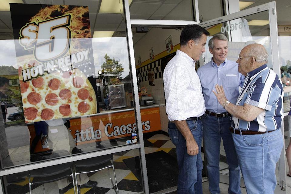 Republican presidential candidate, former Massachusetts Gov. Mitt Romney, left, and Sen. Rob Portman, R-Ohio, center speak to a veteran after buying a pizza at a Little Caesers, Tuesday, Aug. 14, 2012, in Cambridge, Ohio.  (AP Photo/Mary Altaffer)