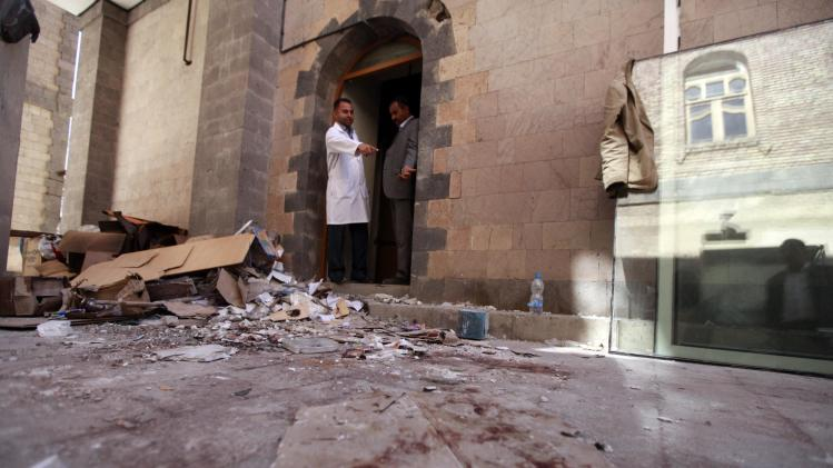 A doctor and survivor of an attack on the Defence Ministry, points at blood inside the hospital at the scene of the attack during a tour at the ministry in Sanaa
