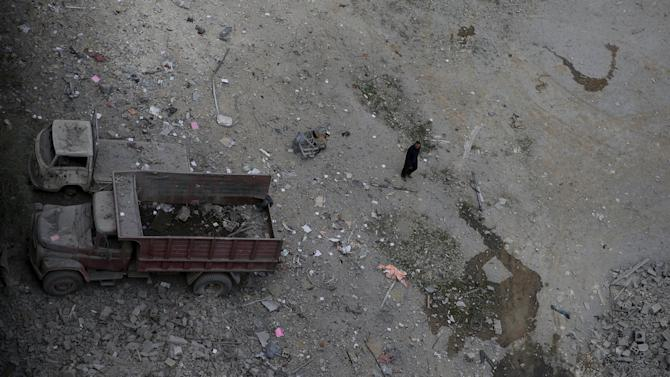 A man inspects the damage at a site hit with airstrikes by pro-Syrian government forces in the rebel held Douma neighborhood of Damascus