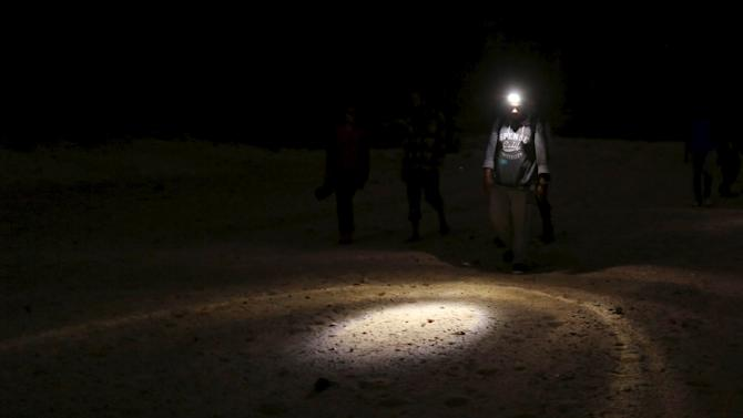 A hiker uses a flash light to see the ground as he walks in the Wadi Rum area in South Sinai